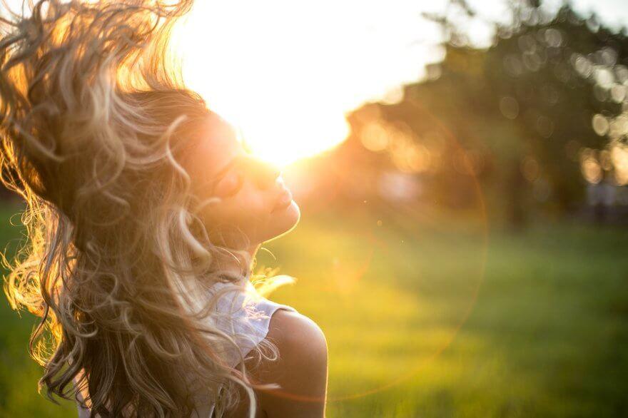 Eine Frau, die ihre blonden Haare im Sonnenuntergang künstlerisch nach hinten wirft.