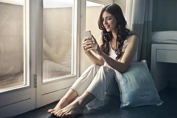 Eine Frau mit braunen welligen Haaren im lockeren Pyjama am Fenster sitzend mit Handy in der Hand.