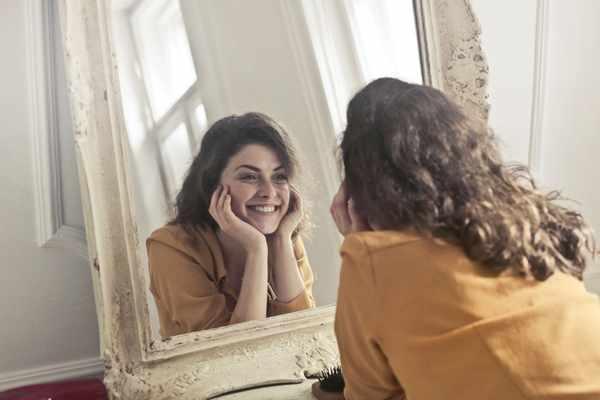 Eine Frau in orange-gelber Bluse grinsend vor dem Spiegel.
