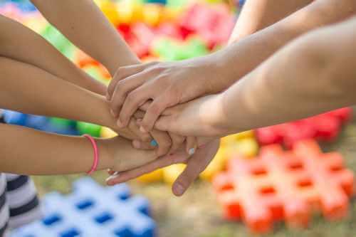 7 Hände von Menschen, die alle in die Mitte greifen und ihre Hände auf eine Hand legen. Verbundenheit.