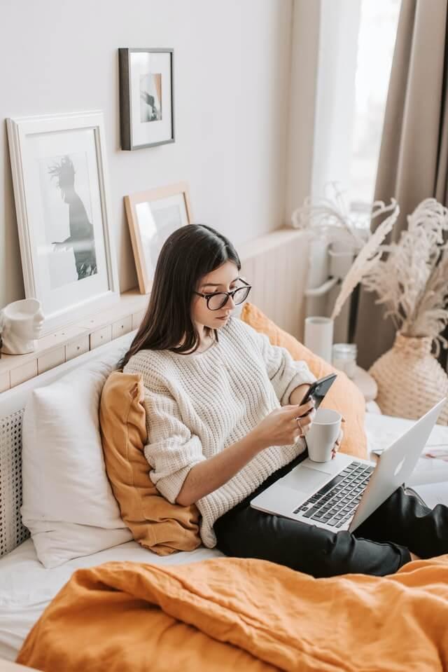 Frau, die auf einem Bett sitzt mit Laptop auf dem Schoß und Handy und Teetasse in der Hand.