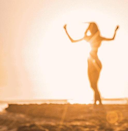 Die leuchtende Silhouette einer Frau, die im Sonnenuntergang verschwommen tanzt.