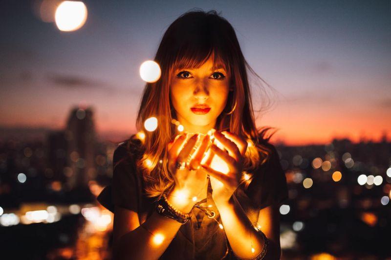 Eine Frau, die eine Lichtkugel in der Hand hält. Im Hintergrund die Stadt in der Dämmerung leicht verschwommen. Sie blickt in die Kamera und mehrere Lichtfunken gehen vom Ball weg in die Nacht hinaus.