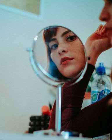 Eine Frau, die einen kleinen runden Standspiegel schaut.