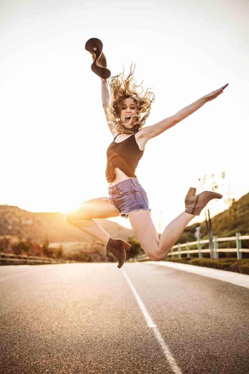 Eine Frau mit blonden lockeren Locken, die auf einer Asphaltstraße im Sonnenuntergang hochspringt und die Beine schweben in 1 Meter Höhe. Sie schaut lachend und keck in die Kamera, streckt den linken Arm komplett gerade nach hinten, der rechte Arm streckt voller Freude einen Hut gen Himmel.