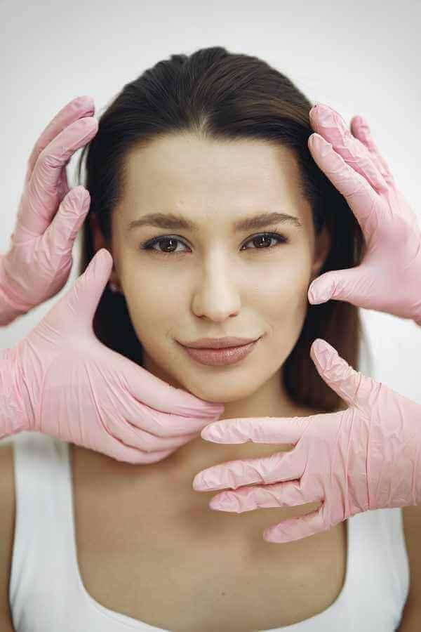 Ein Frauengesicht frontal zur Kamera, 4 rosa Hände um ihr Gesicht, die sie leicht an der Haut im Gesicht anfassen.