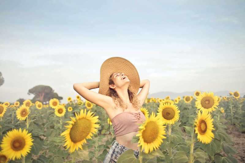 Eine Frau, die lachend mit Sonnenhut im Sonnenblumenfeld steht.