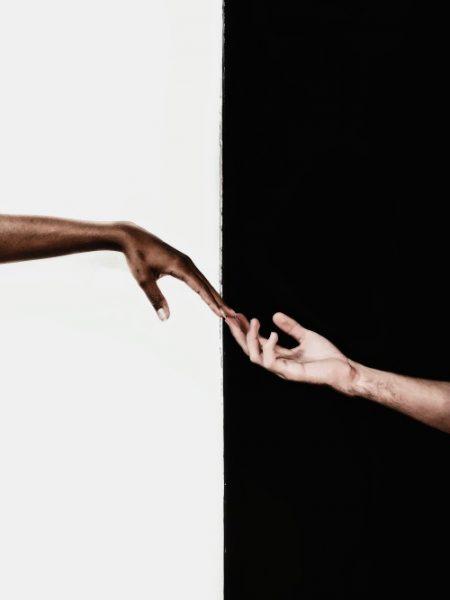 2 in der Mitte getrennte Flächen im Hochformat. Links ist eine weiße Hälfte, rechts eine schwarze. Links in der weißen befindet sich eine Hand einer dunkel pigmentierten Frau, die von linken Fotorand zur mittigen Grenze ausgestreckt ist, und eine Hand eines weißen Mannes, die vom rechten, schwarzen Rand kommt, an den Fingerspitzen berührt.